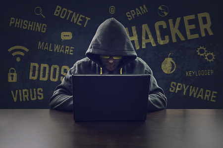43768357 - hooded cyber criminal stealing secrets with laptop